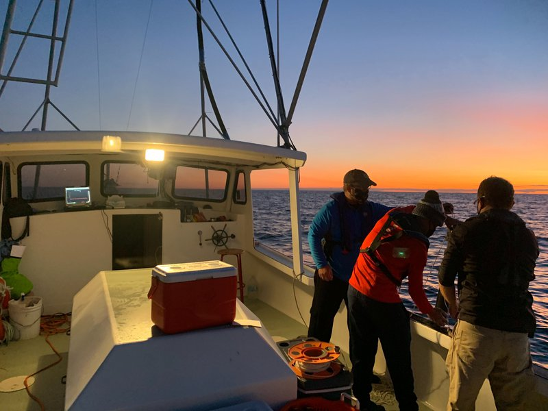 Three men lean over the starboard side of the boat, silhouetted by a blazing orange and blue sunset.