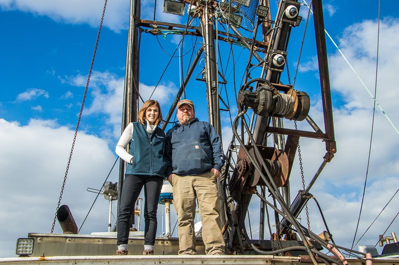 Fisheries Technical Assistance Program Manager Heather Cronin stands aboard a ship with recently mounted electronic monitoring cameras alongside a fisherman.