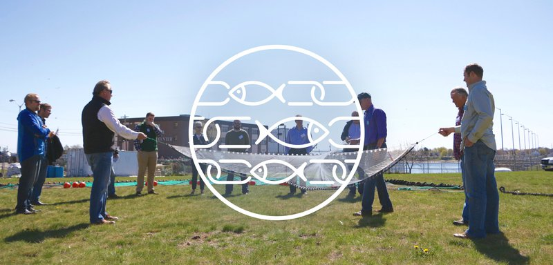 This image has a white circle with white fish drawn as links in chains inside, centered over a group of fishermen gathered outside holding a fishing net.