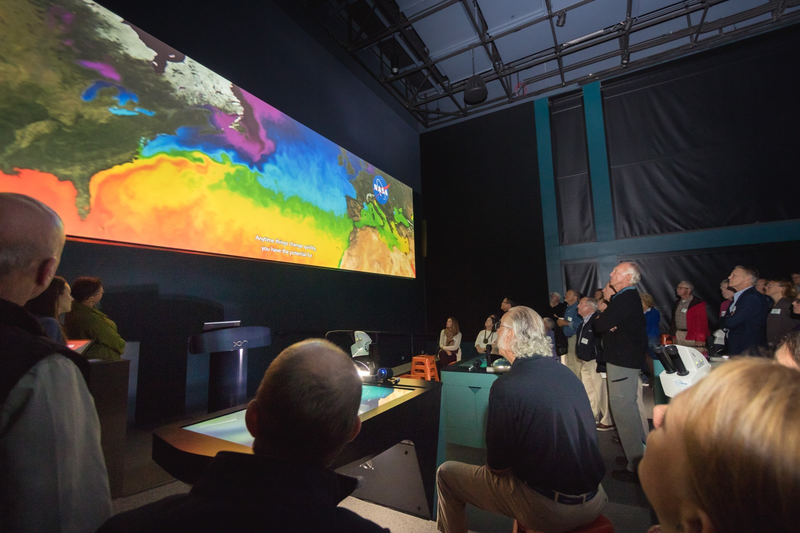 Adults gather in a large dimly lit room and look at a colorful digital display of the Gulf of Maine on a wall on the left side of the photo.