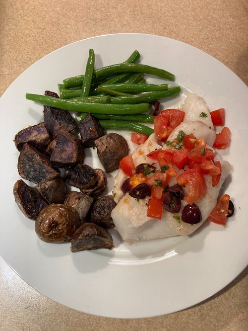 Green beans, mushrooms, and white hake topped with tomato and olives sits on a white plate on a brown table.