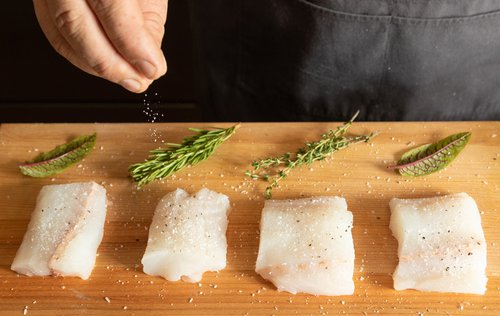 A chef sprinkles salt on fish fillets on a wooden cutting board with herbs next to the fillets