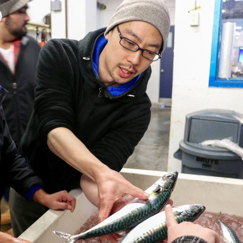 Japanese chef in a black zip up jacket and a gray hat holds a slender fish out to a customer in his right hand.