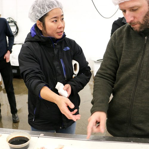 A Japanese woman in a black jacket and a white hair net holds her right hand out as she discusses seafood with a man in a green sweater and a white hairnet.