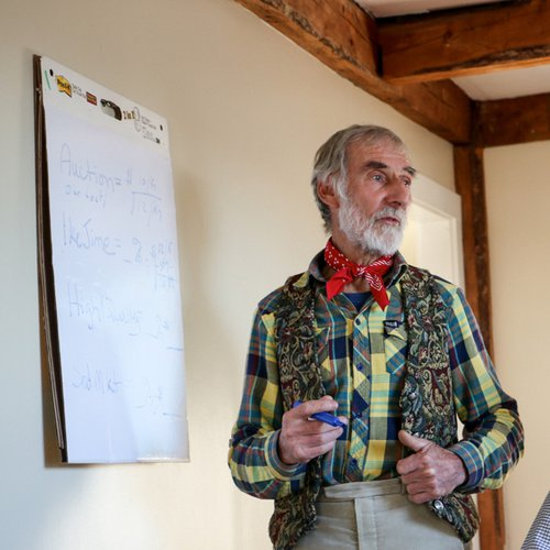 Fishermen Chris Bean stands in front of a large white notepad in a yellow plaid shirt, with a floral vest, and a red bandana tied around his neck like a bowtie.